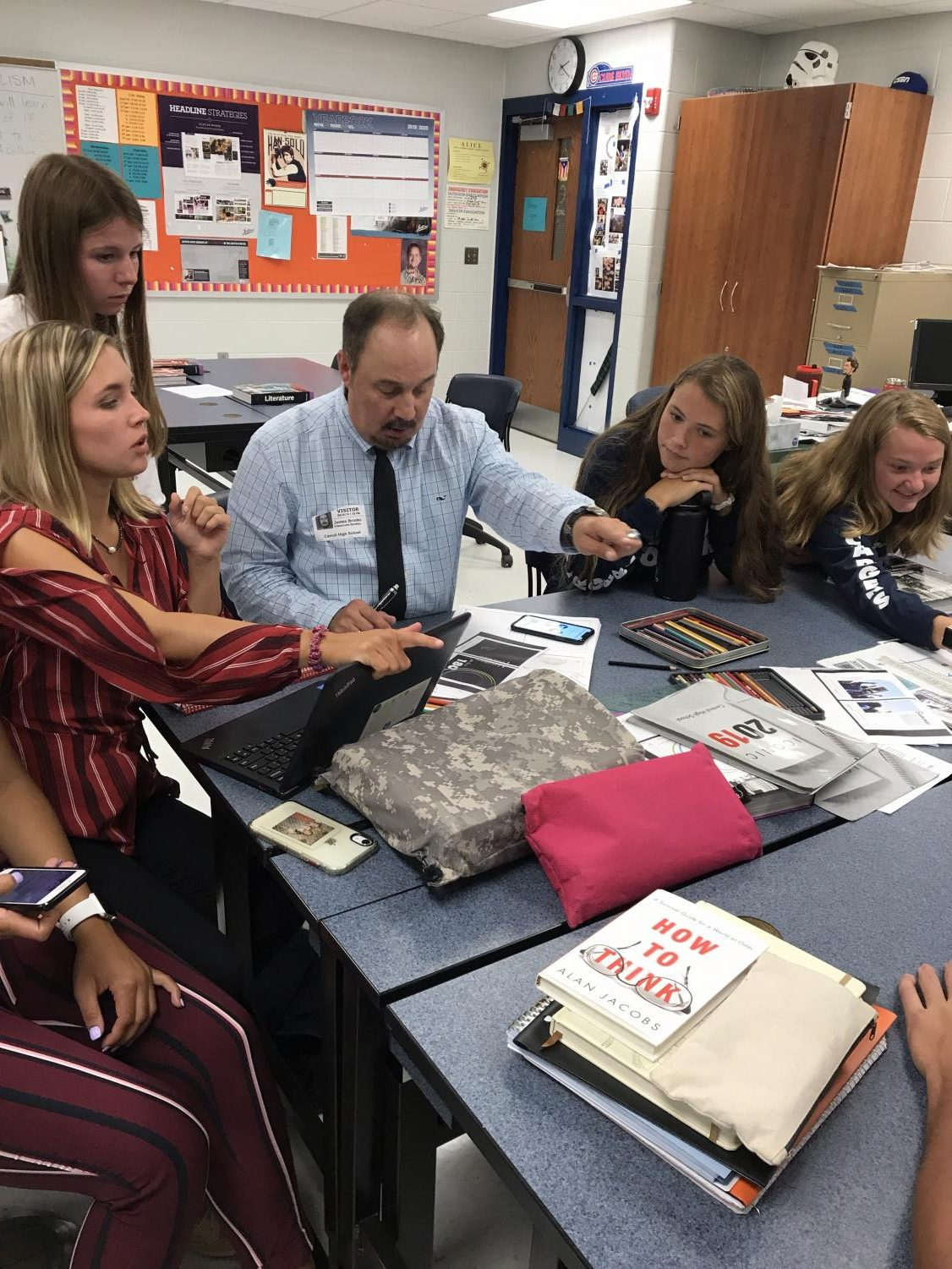 Josten's Designer Rick Brooks works with Editor-in-Chief Graham Ruselink, Student Life Editor Sydni Amick, Sports Editor Liz Knorr and Clubs Editor Kelsi Hoot on the cover of the 2020 Cavalier yearbook on August 26, 2019. Mr. Brooks comes to Carroll High School to help bring the editors' vision to life every year. Photo by VM Smith.