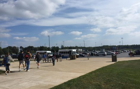 Students walk out of school at the end of the day into the school parking lot to drive home.